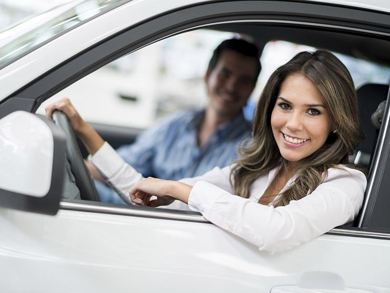Couple driving a new car